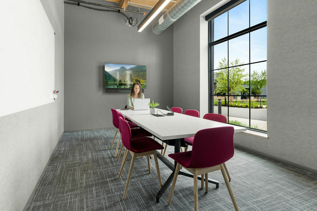 conference room with pink upholstered chairs, white table and woman sitting at end of table on computer