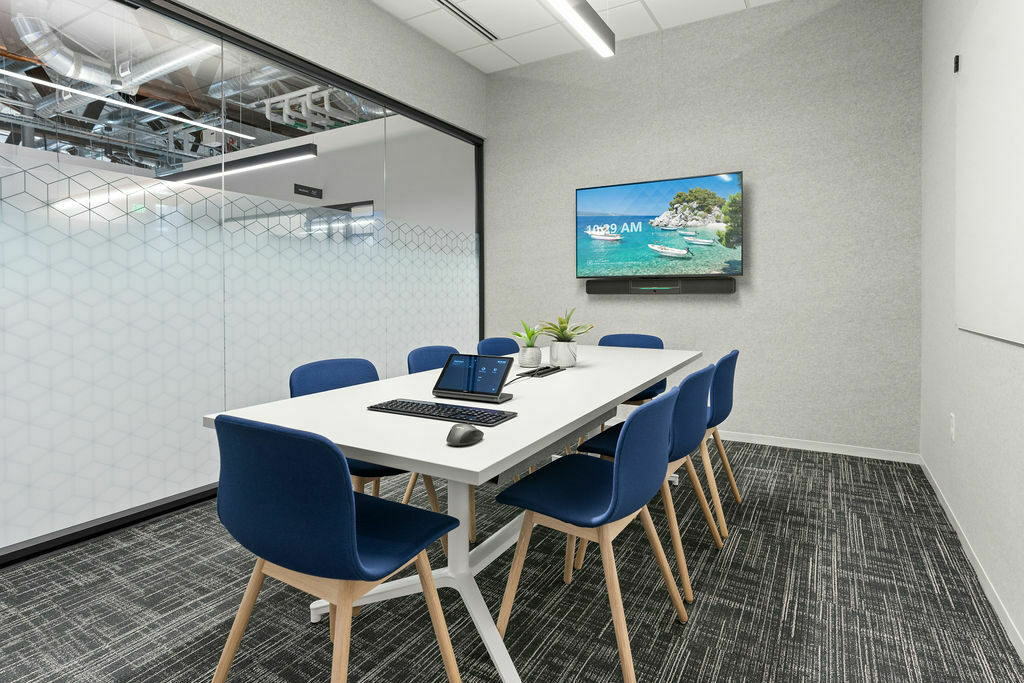 conference room with blue upholstered chairs, white table, tv and DIRTT glass walls