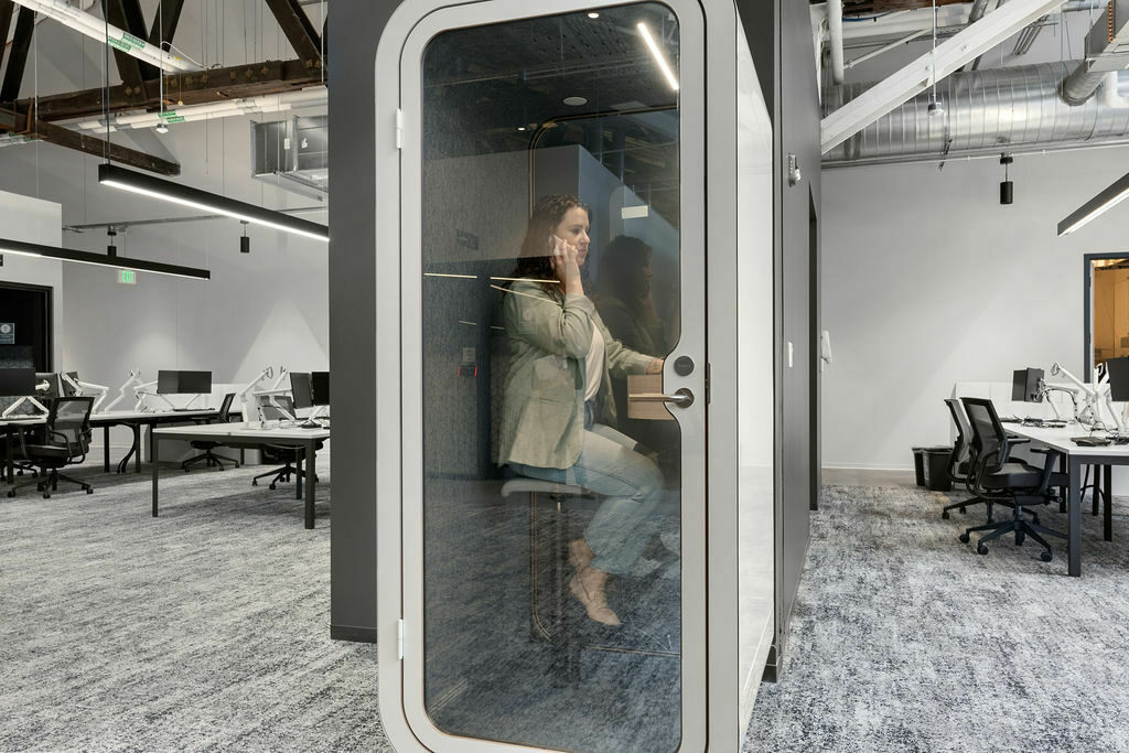 woman using Framery phonebooth on phone