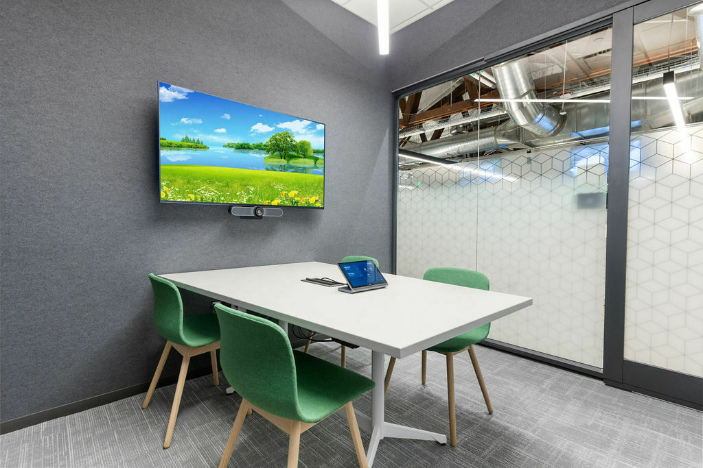 small huddle room with green upholstered chairs, a white table and a tv